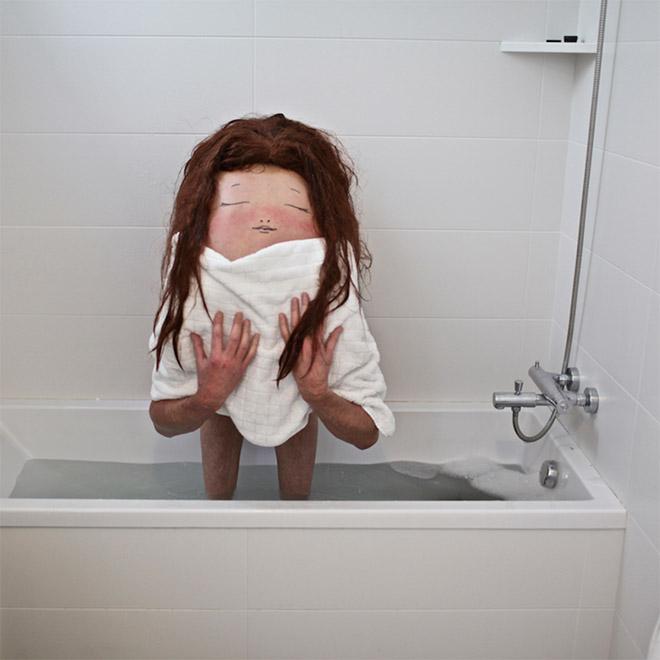 Creepy body art creature standing in a bath tub.