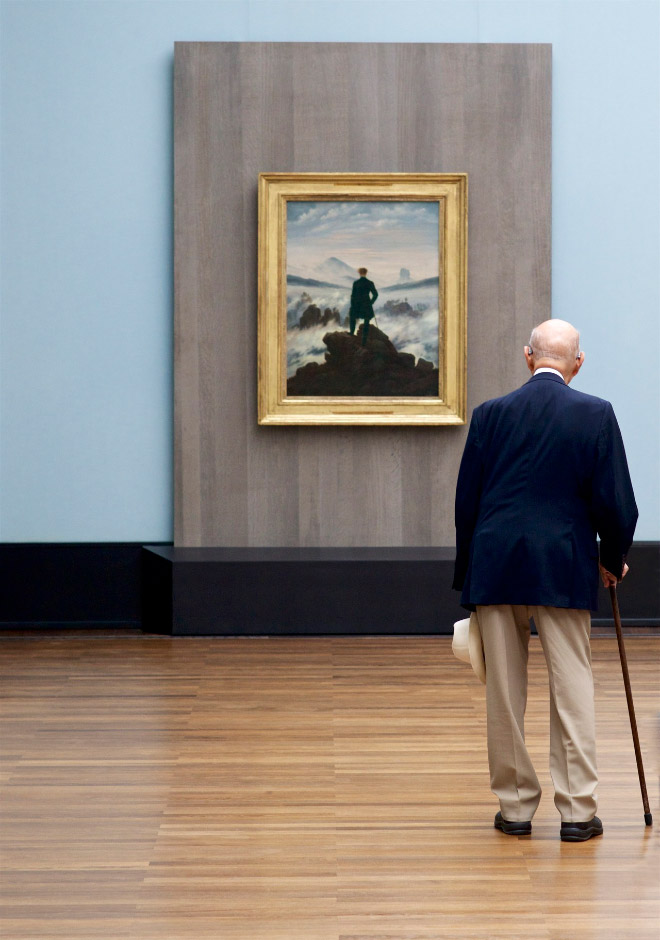 Old man perfectly matching a painting in an art museum.