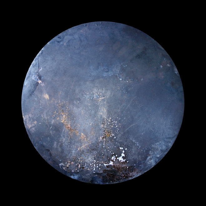 Old frying pan that looks like a distant alien planet.